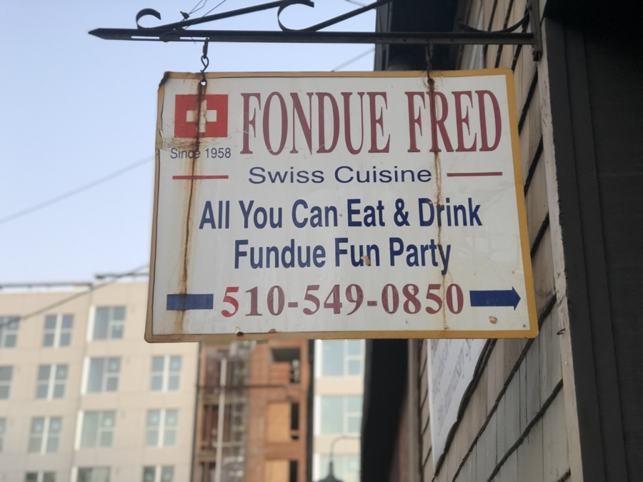 "A sign for Fondue Fred restaurant in Berkeley states: ""Since 1958 Fondue Fred Swiss Cuisine All You Can Eat & Drink Fundue Fun Party 510-549-0850."""