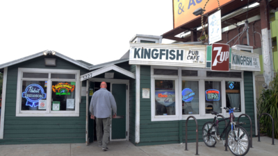 A man walks into the front entrance of the Kingfish Pub and Deli on Telegraph Avenue.