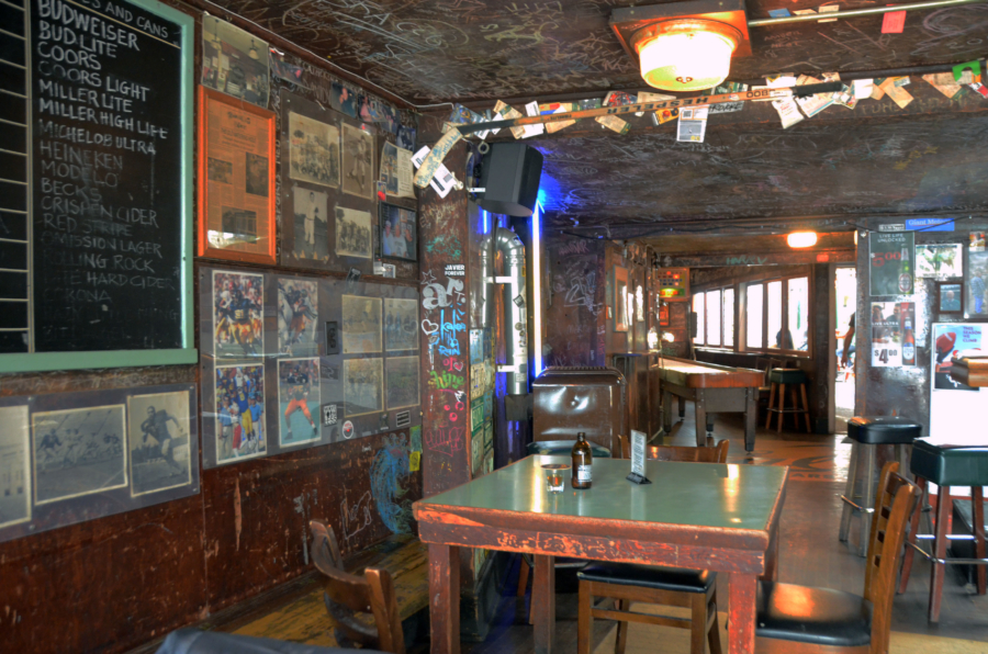 The front room at The Kingfish Pub, featuring decades worth of grafitti scribbles and faded sports ephemera plastering almost every surface of its walls and ceilings.