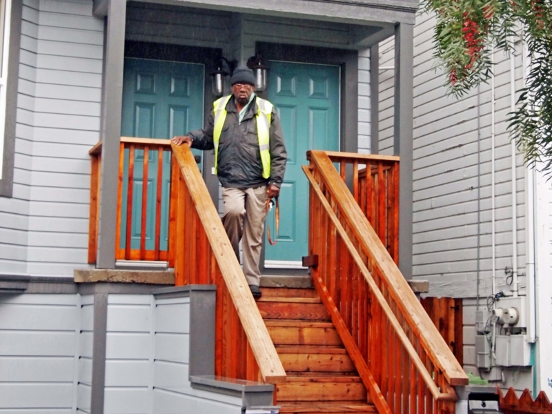 man standing on steps of house