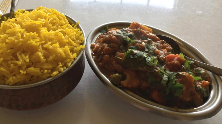 A serving of yellow rice and a platter of vegetable curry topped with cilantro at Mehak Indian Cuisine in Berkeley
