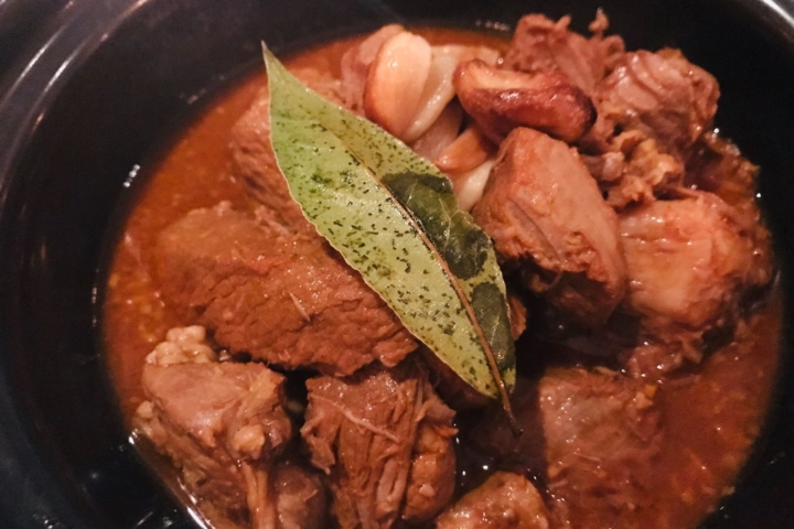 A close-up of pork adobo with a bay leaf garnish.