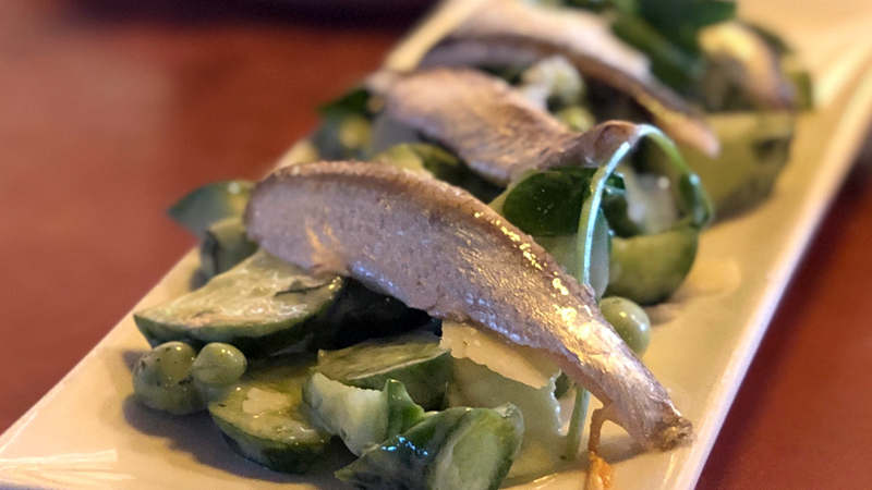 A plate with pea salad topped with anchovy at Shakewell in Oakland.