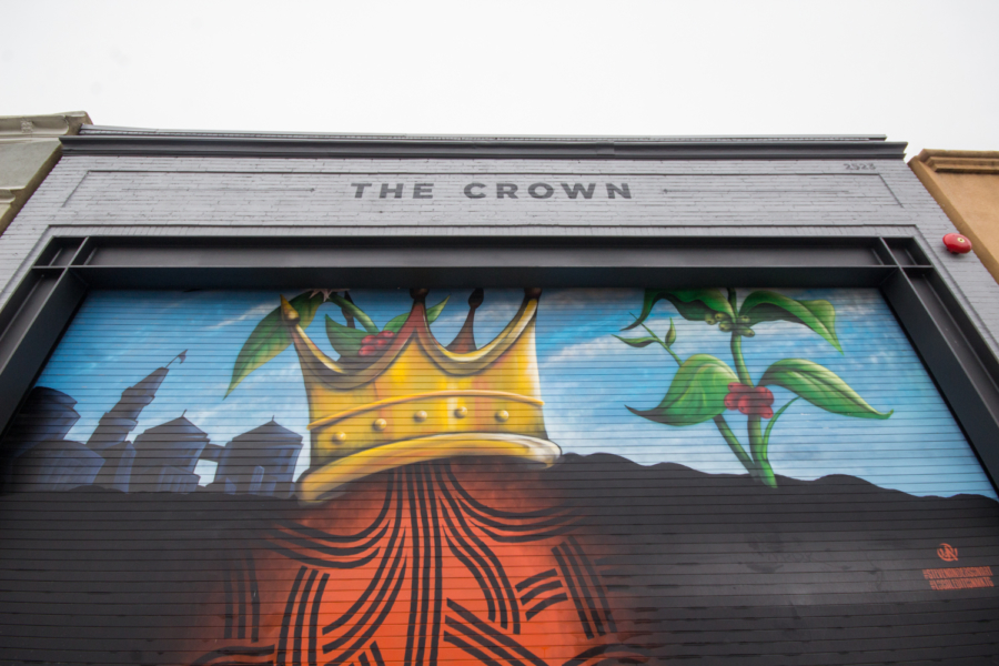 A painted roll-up garage shows an illustration of the Oakland tree with a crown on top and coffee beans growing from the ground at the building housing the Crown, a new coffee space in Oakland's Auto Row.