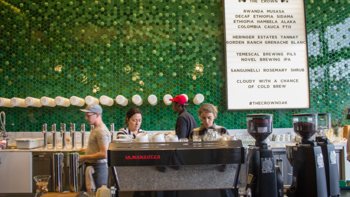 Three café employees stand behind a counter preparing coffee drinks at The Crown Lab and Tasting Room in Oakland. There is a bright green tile wall behind them with a large white menu listing coffee farmers who supply the coffee.