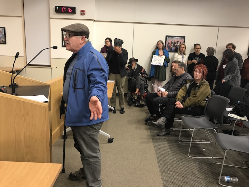 A man speaks at the podium at a City Council meeting