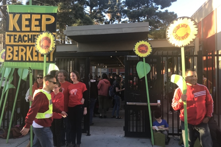 "Several red-clad people stand outside the gate to a courtyard, holding tall signs shaped like sunflowers. One has a huge sign that says, ""Keep teachers in Berkeley."""
