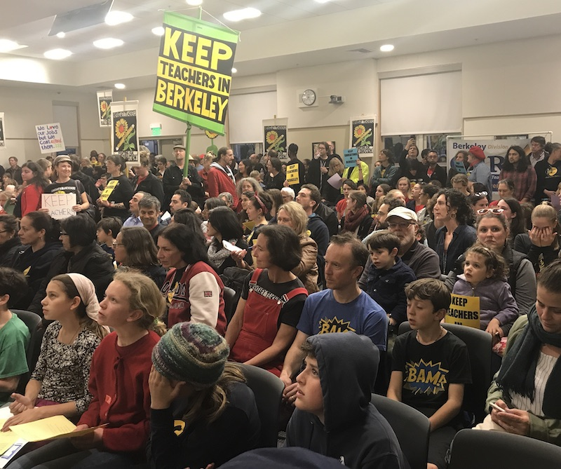 """Dozens of people are seated in a meeting room. Several are kids. One has a big sign that says, """"Keep teachers in Berkeley."""""""