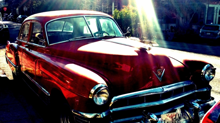 red Cadillac with sun streaming on it