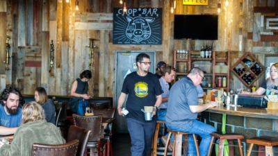 Customers sit at tables and at the bar at Chop Bar in Jack London Square.