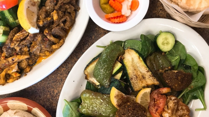 Plates of Middle Eastern dishes, like shawarma, grilled vegetables, pickles, more from Petra Middle Eastern Cuisine in Livermore.
