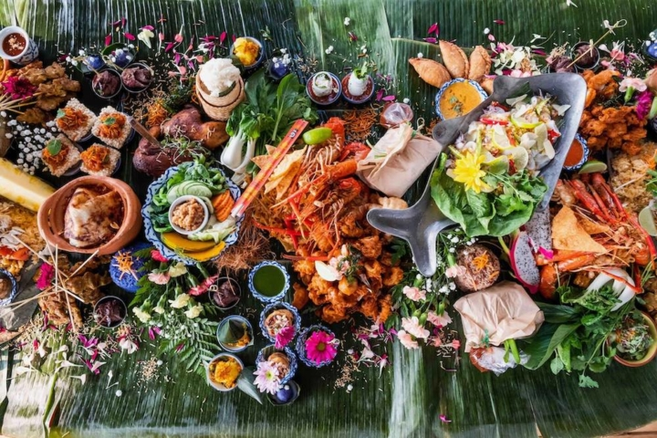 A table set with banana leaves with a spread of Thai and Lao foods.