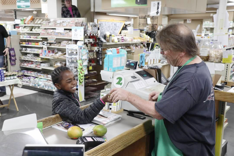 A cashier helps a young boy at The Food Mill in Oakland.