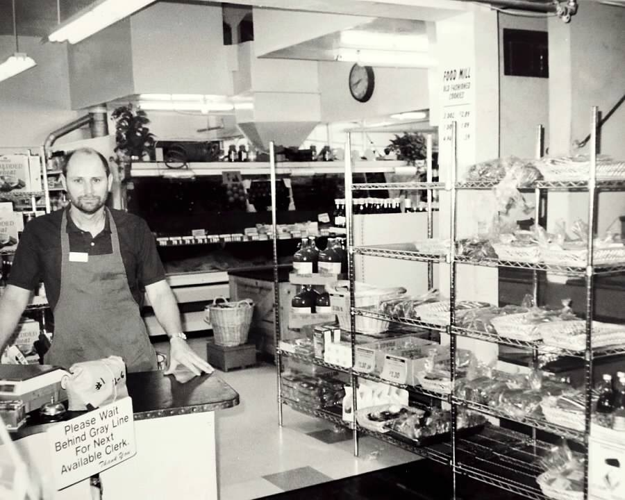 A black and white photograph of Food Mill owner Kirk Watkins working as a cashier at the store in the 90s