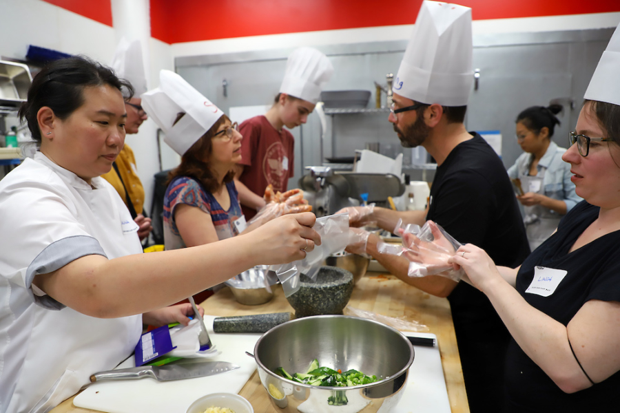 "Chef Selina Lee (left, front) guides participants on making stuffed cucumber kimchi at the ""Nourishing Roots"" event."