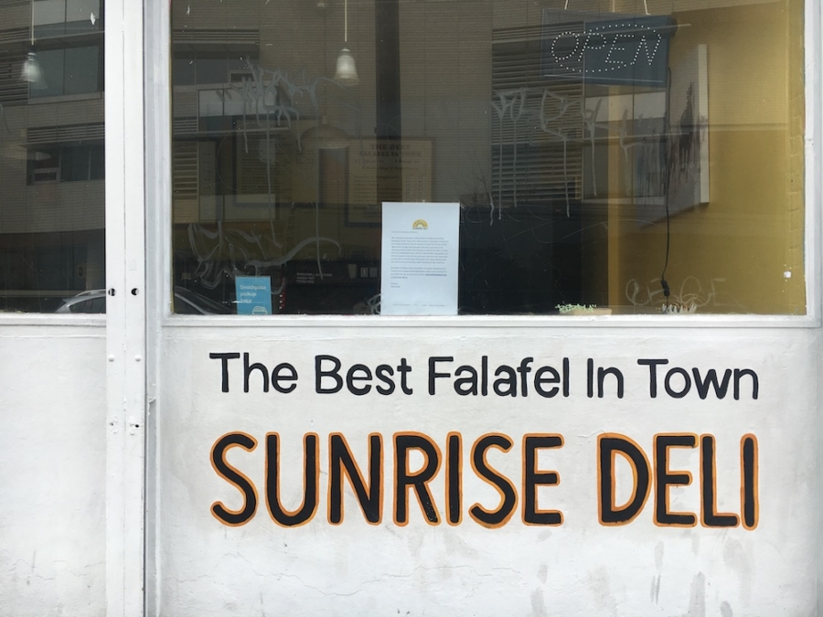 "A painted sign on the outside wall of Sunrise Deli in Berkeley says, ""The best falafel in town Sunrise Deli"""