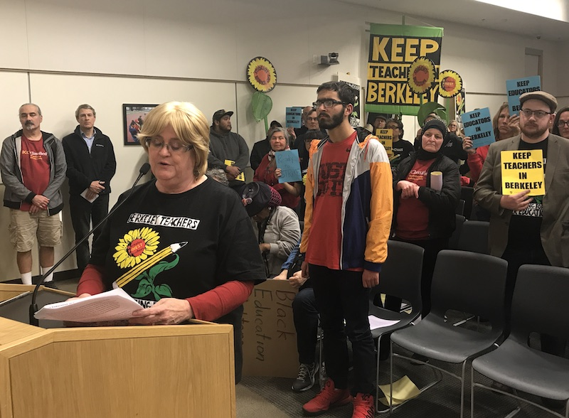 "Woman in teachers union shirt speaks at a podium. Several people are standing behind her, some holding signs that say ""Keep teachers in Berkeley."""