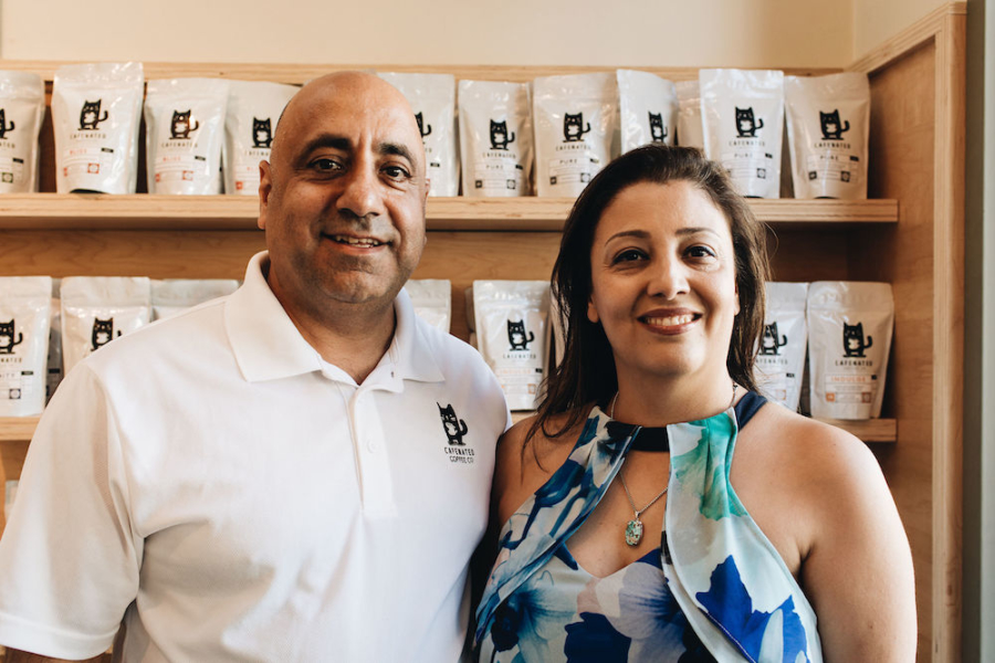 Cafenated Coffee founders Mak and Parisa Jamasbi stand in front of bags of their coffee.