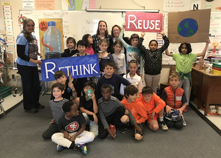 "Group of about 20 kids with a couple adults in the back. Posed photo. Holding signs that say ""reuse"" and ""rethink."""