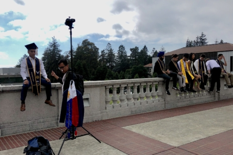 Students in graduation robes sit on wall at UC Berkeley