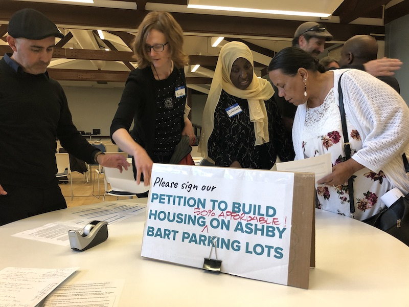 "In the foreground, a sign on a table says ""Please sign our petition to build housing on Ashby BART parking lots."" Four people stand behind the table peering at the materials."