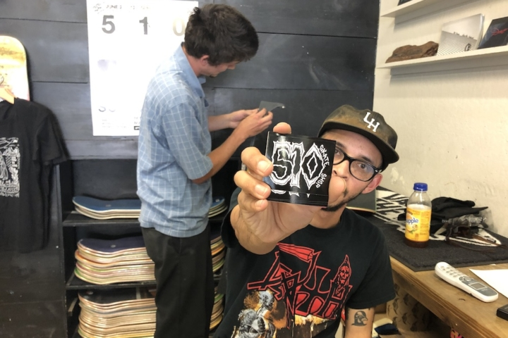 "Guy in his twenties holds out sticker that says ""510."" He's sitting at the desk in a store. Behind him is another employee and stacks of skateboards."