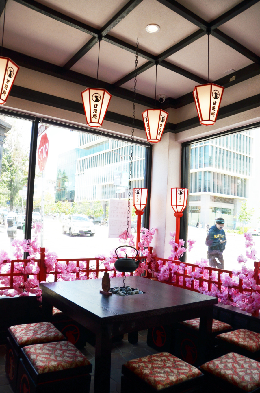 A corner table in the front dining area at Amausaan Uji Matcha in Berkeley is surrounded by windows and decorated with fake cherry blossoms, lanterns and a hanging tea kettle over a table.