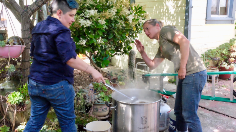 Queers Makin' Beers co-founder Rebecca Sandidge (right) and member Beck Herrick stand over a simmering 11-gallon pot of what will become a kolsch-style ale.