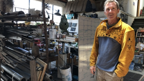 50-something man in a bright yellow decorated jacket stand, smiling, next to stacks of scrap metals and tools.