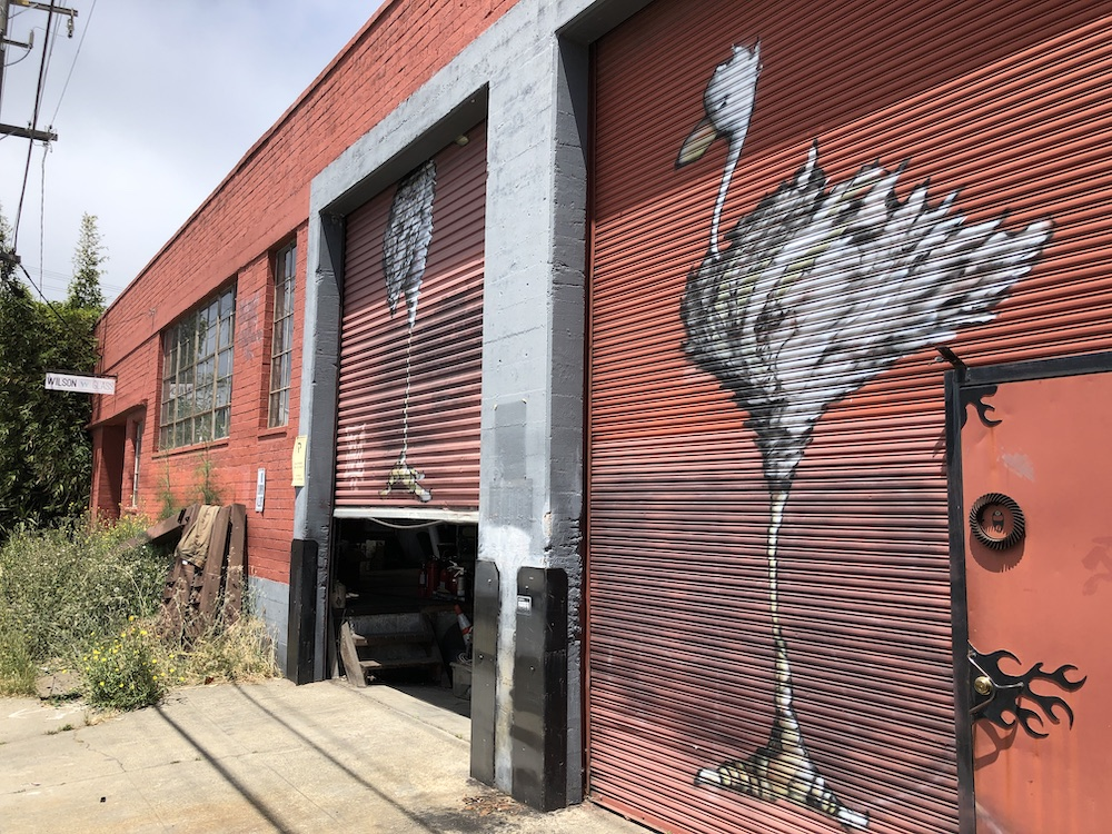 Red garage doors with birds spray painted on them.