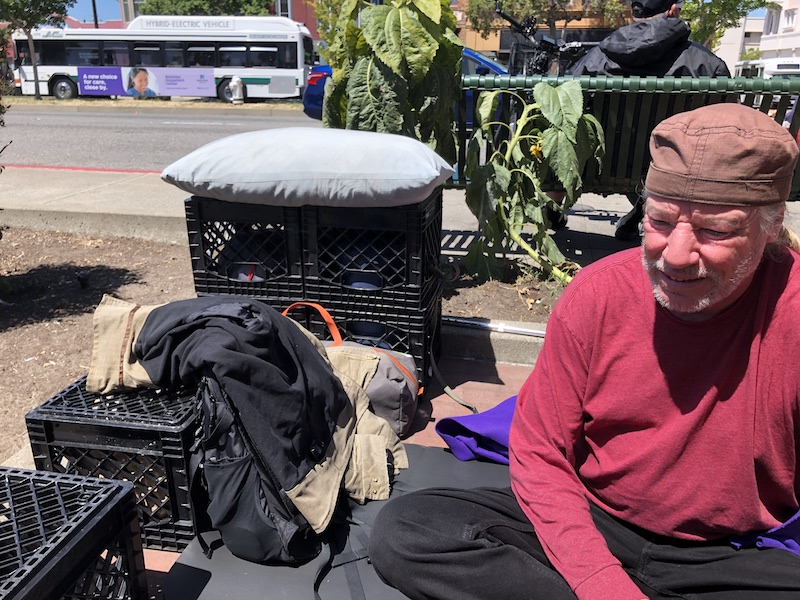 Man in his 60s in a red shirt sits on a mat on the sidewalk, next to crates with some stuff on top of them.