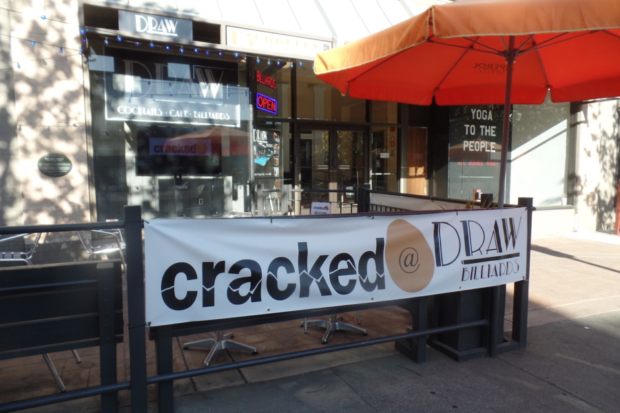 A sign for Cracked hangs on the outdoor fence outside of Draw Billiards in downtown Berkeley.