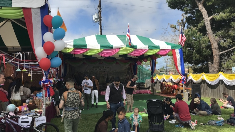 Colorful circus-like tent. People sitting on grass in front of it, eating.