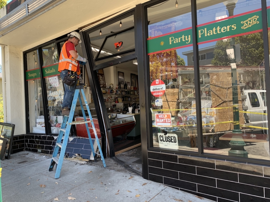 A worker makes temporary repairs to the damaged entryway at Zarri's Delicatessen in Albany.
