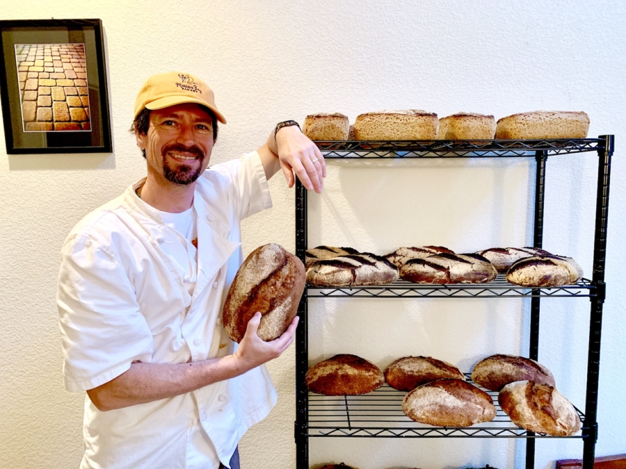 Marina Bay Bakery founder Dan Gildor stands next to a shelf of baked breads.
