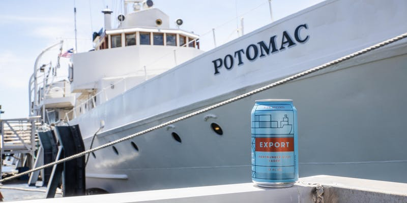 A can of Fort Point Export beer sits at a dock with the USS Potomac in the background.