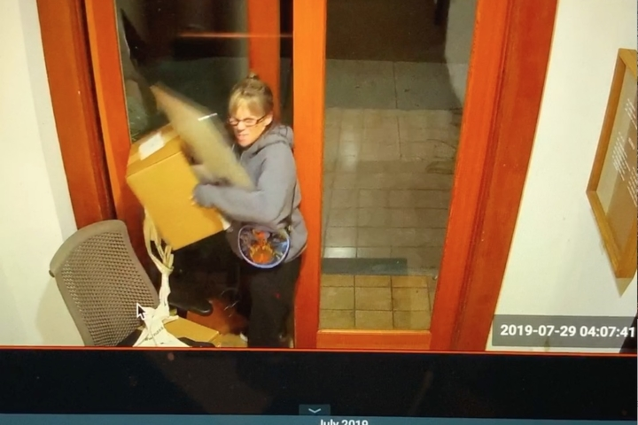 Surveillance footage shows a woman holding a computer and a box by a door.