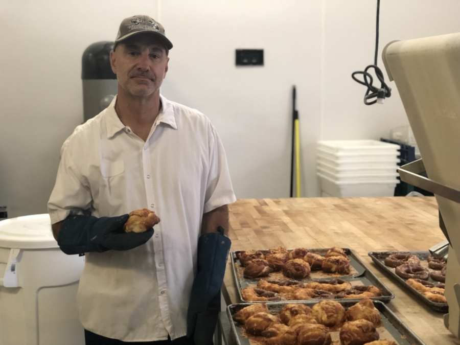 Squabisch founder Uli Elser holding a pretzel while standing next to a tray full of freshly baked pretzels in a commercial kitchen.