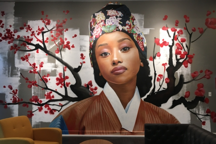 A large mural of a black woman in traditional Korean garb by Korean artist Chris Chanyang Shim graces the wall upstairs at Wrecking Ball in Berkeley.