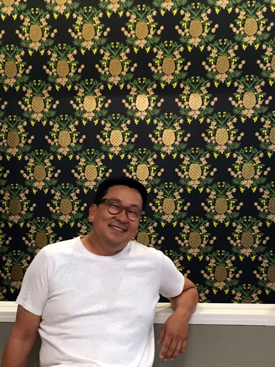 Wrecking Ball co-founder Nick Cho poses in front of the pineapple wallpaper at the Berkeley location.