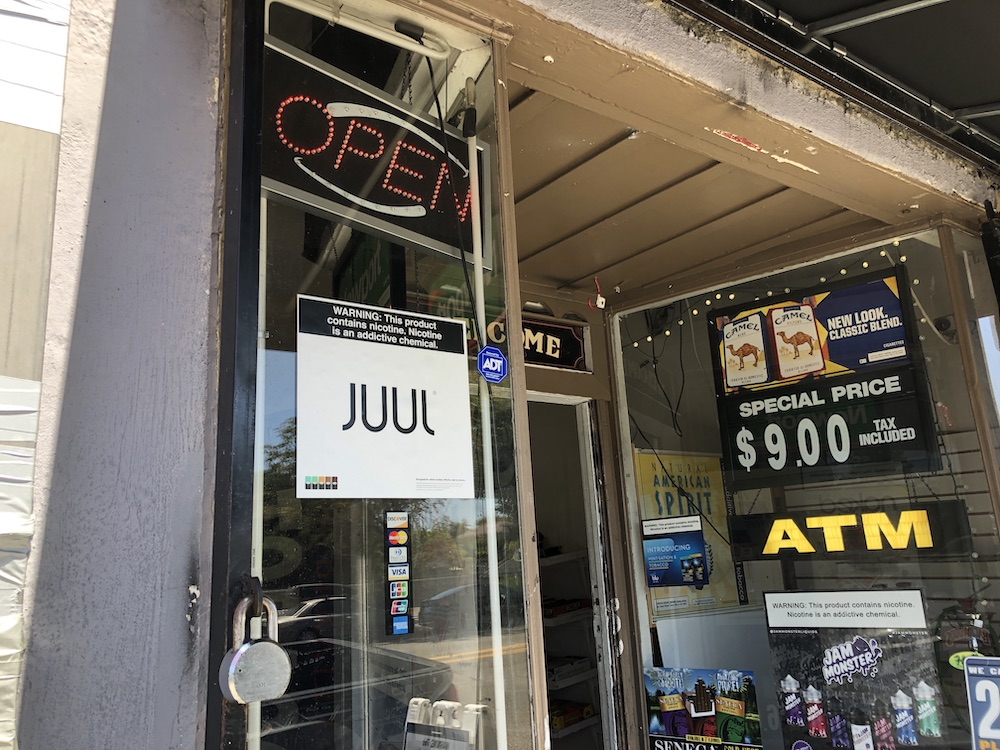 storefront, has ads for Juul, cigarettes, ATM