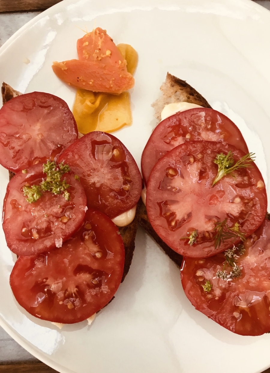Dry-farmed Early Girl tomato tartine, with a creamy housemade aioli and delicate floral blossoms at Bar Sardine.