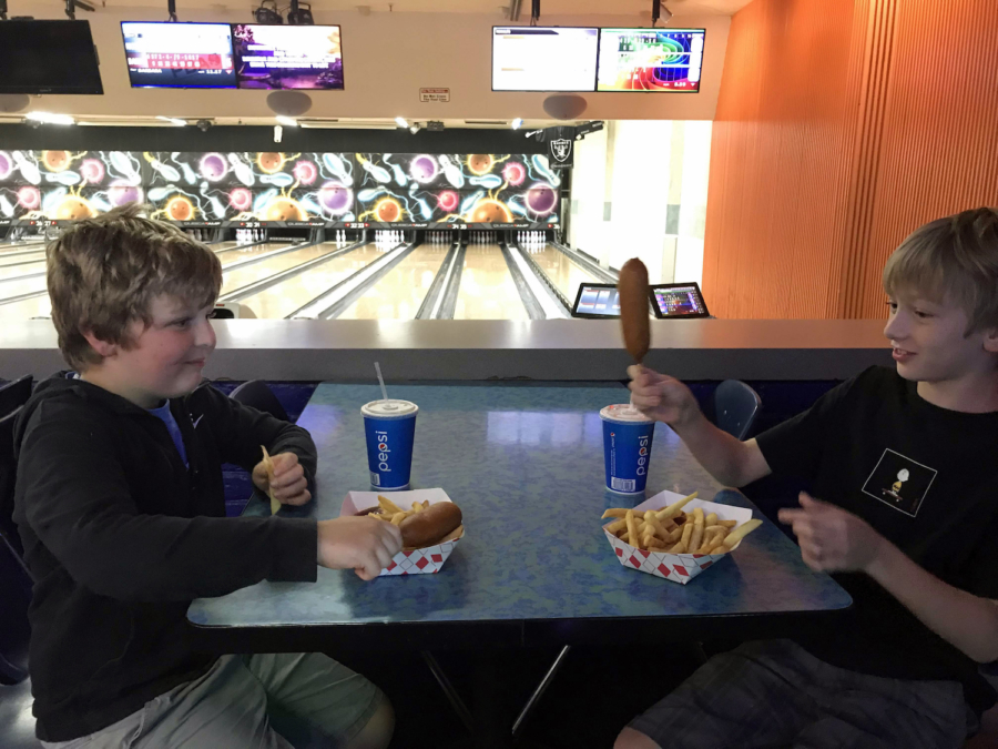 Two young boys enjoy corn dogs, fries and fountain drinks at Albany Bowl.