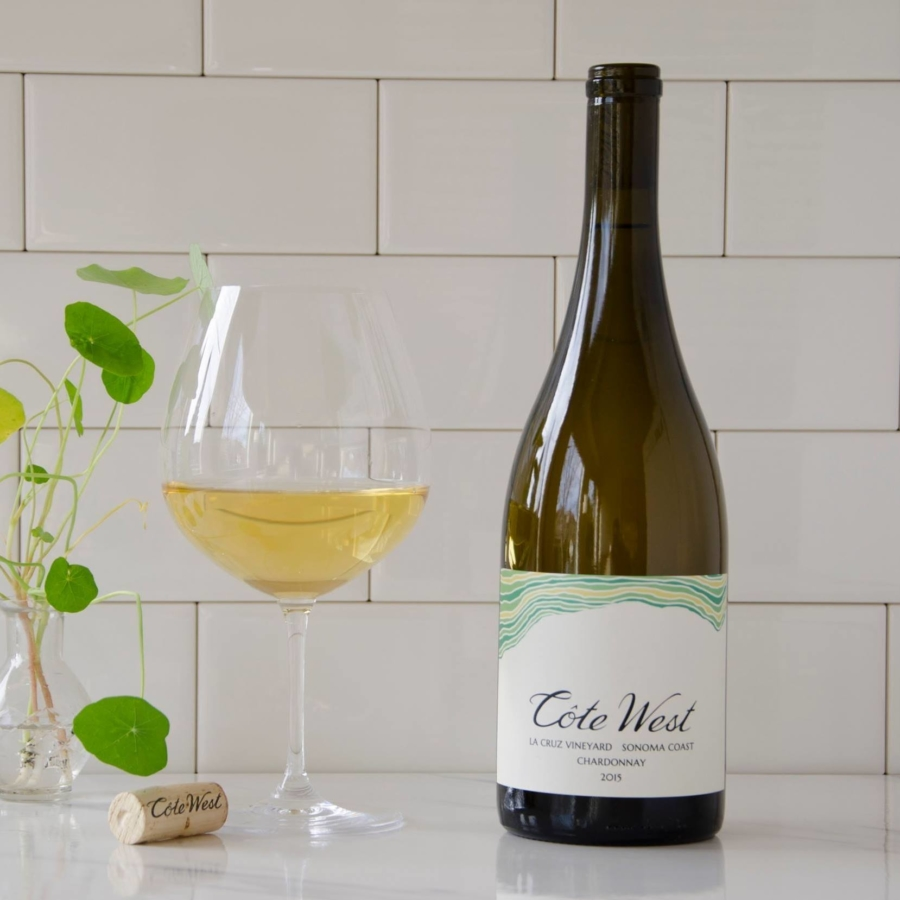 A glass filled with Côte West Chardonnay on a table with an open bottle. Photo: Côte West