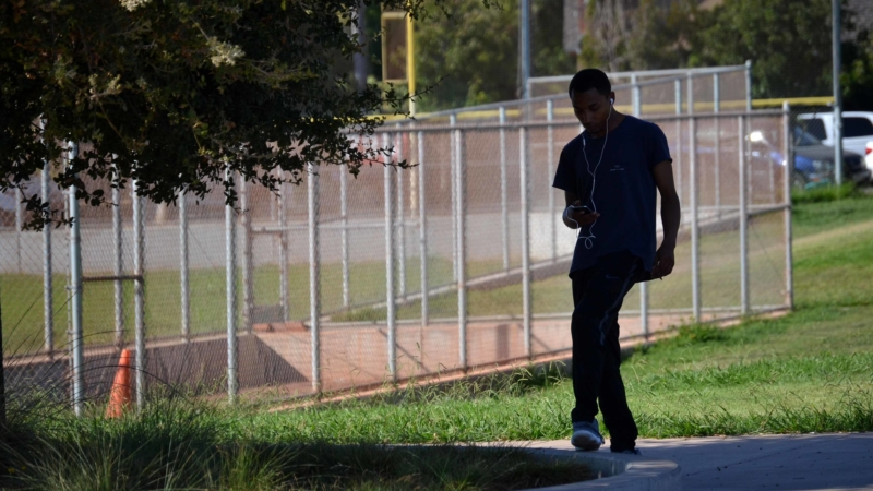 young man walking along park while listening to music