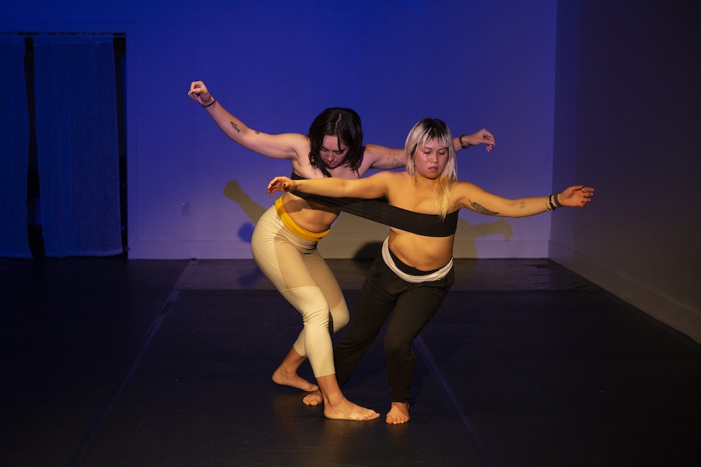 Two people dance on a stage; the same elastic band stretches across both their chests.