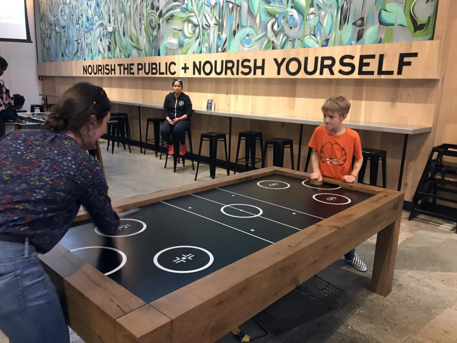 A mother and son play air hockey at Public Market Emeryville.