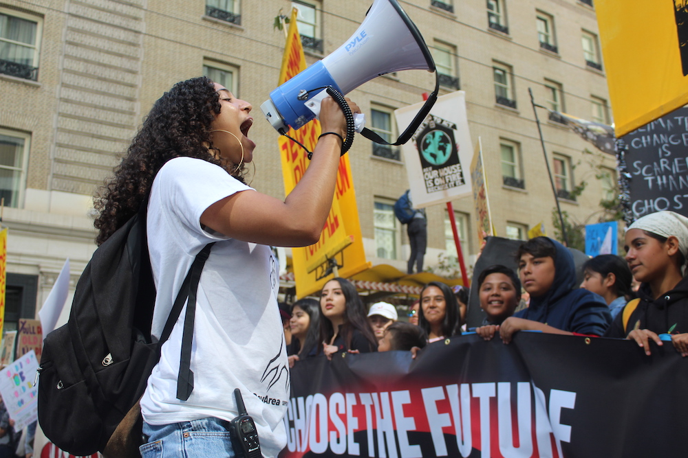 A girl yells into a megaphone, with young protesters in the background