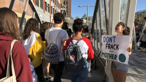 "Young people file into a subway entrance; one girl stands on the side with a sign that says ""Don't frack with Mother Earth."""