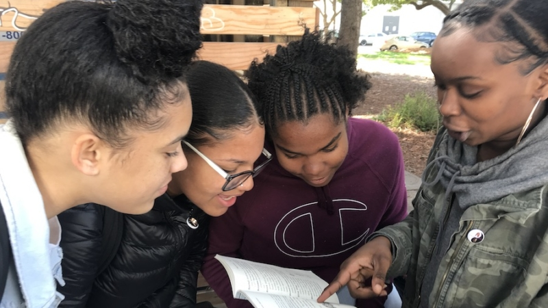 Four girls point at a book and smile